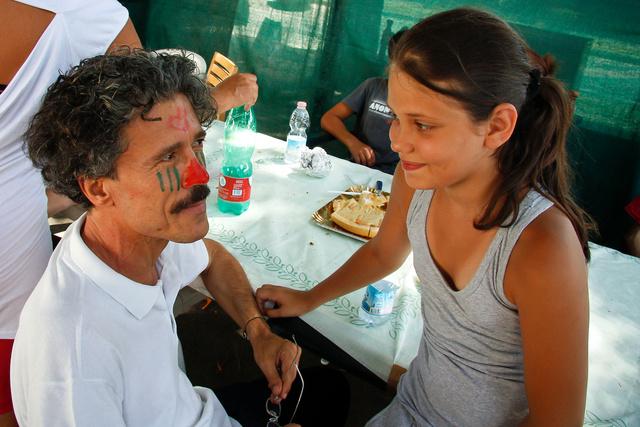 Una bambina ed un educatore durante la festa organizzata da Davide nelle Vele di Scampia