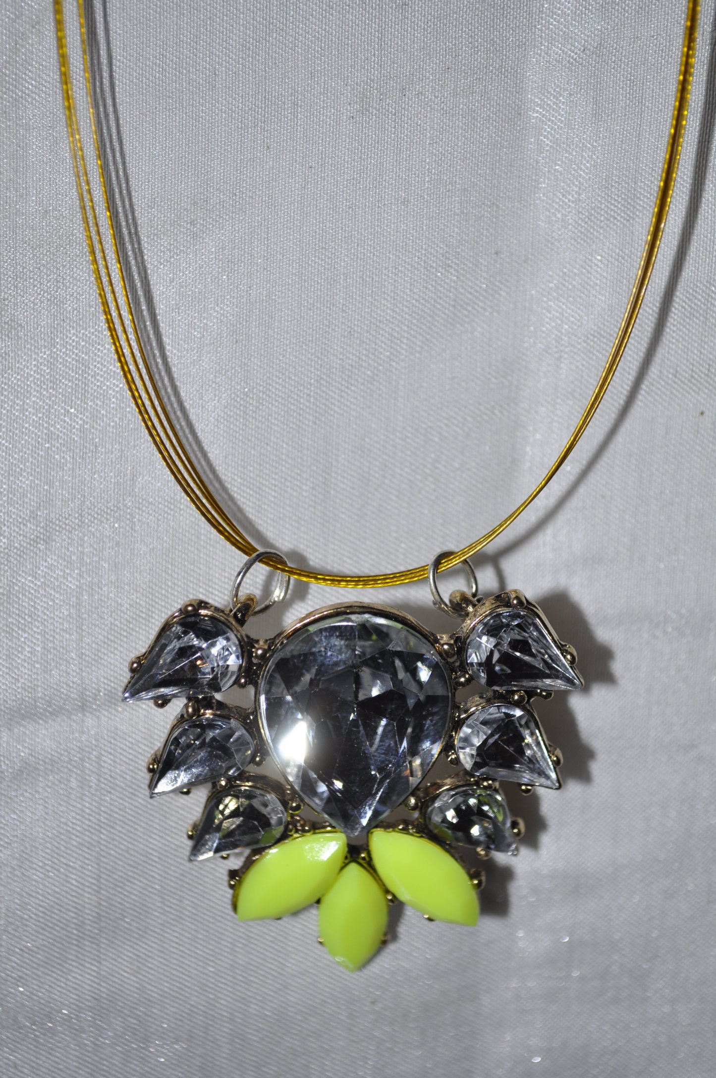 CLEAR AND LIME STONE added to a gold neck rope.