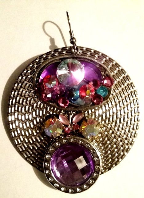 "2.5"" round earrings with multicolored stones and embellishments."