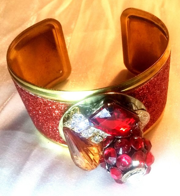 RED/GOLD CUFF with multicolored stone embellishments.