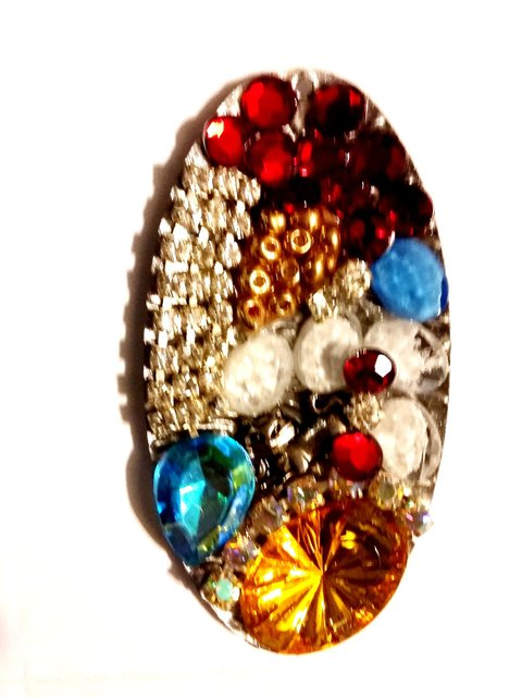 OVAL SHAPE NECKLACE PENDANT WITH MULTIPLE STONES AND EMBELLISHMENTS.