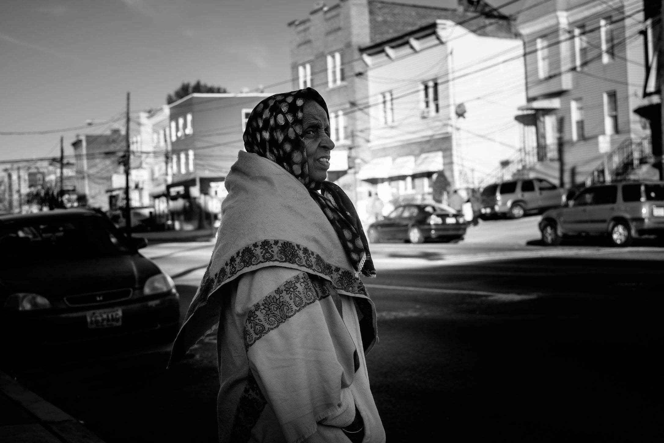 Older woman with head wrap waiting to cross the street.jpg