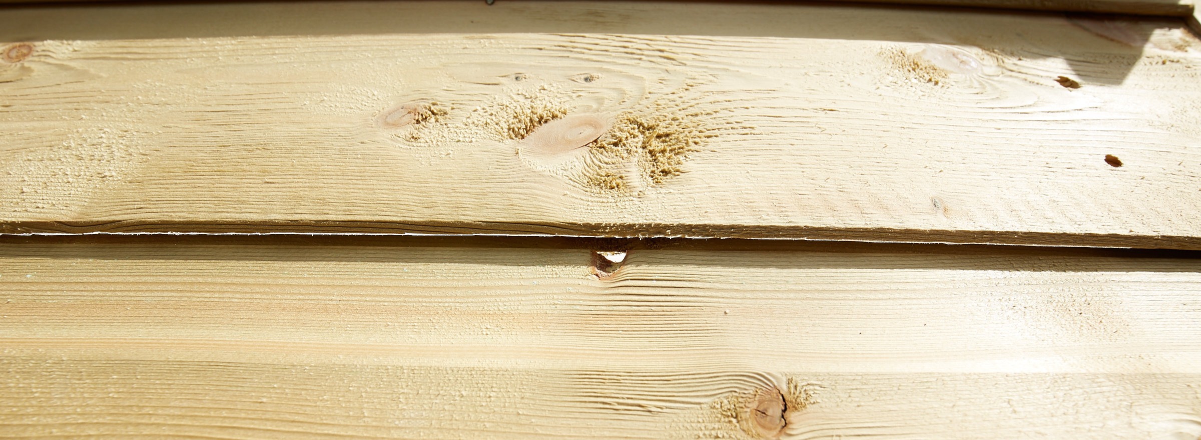 Photo showing gap in tongue and groove of back panel of shed