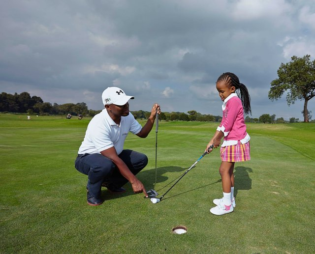A father and daughter at the golf course