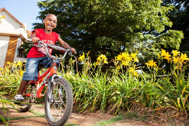 A young boy rides in his bicycle - physical activity for children promotes good health.