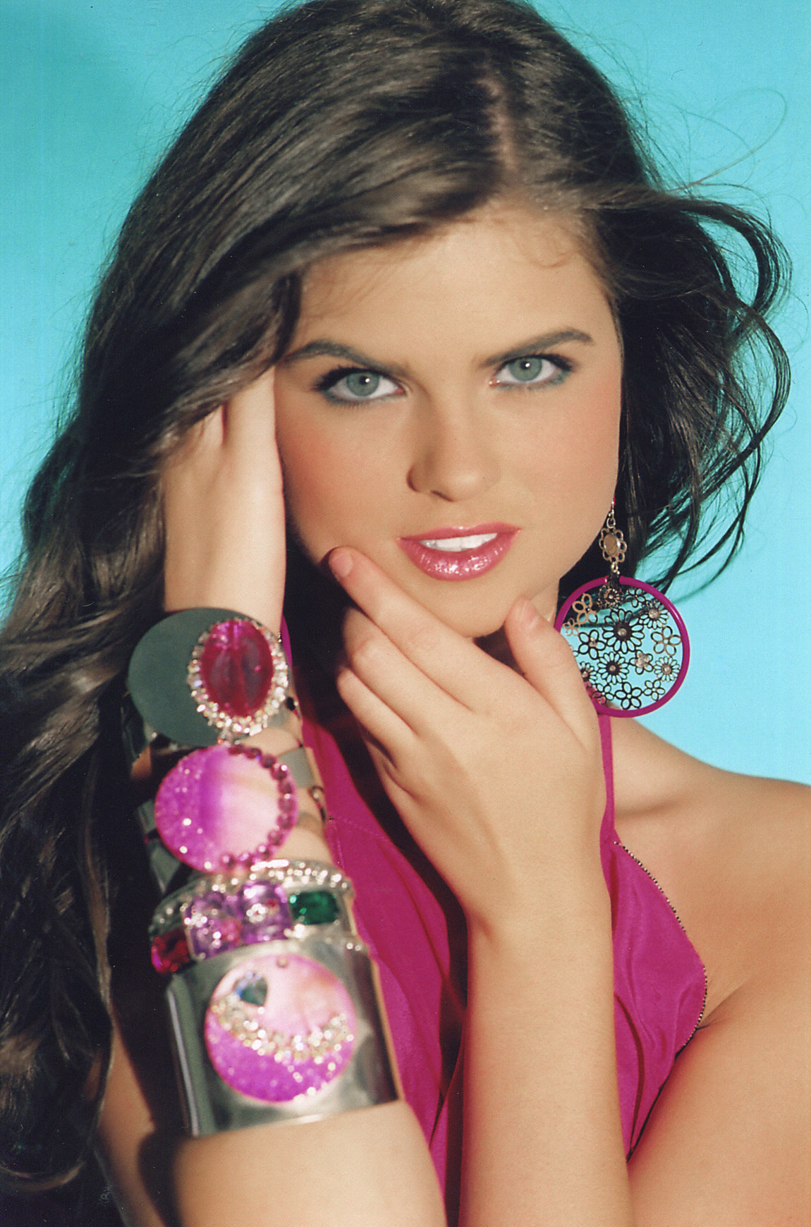 REBECCA is wearing 4 wide cuffs with colored stone embellishments.