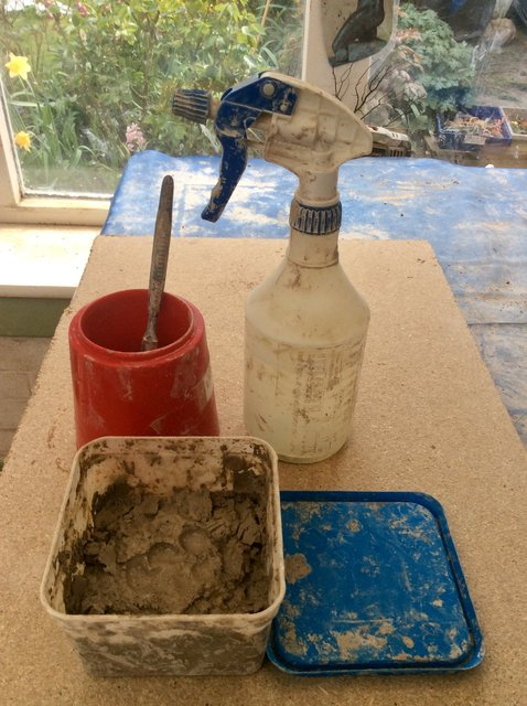 water spray  or water jar with brush; clay recycling  in a plastic tub