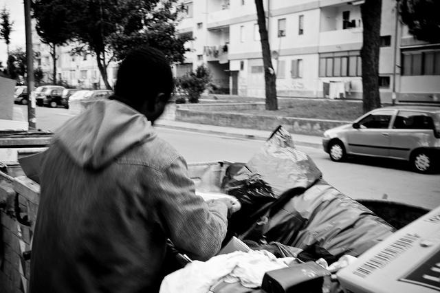 Un uomo cerca tra i rifiuti