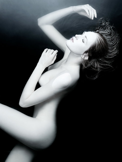 Young nude woman floating in dark water