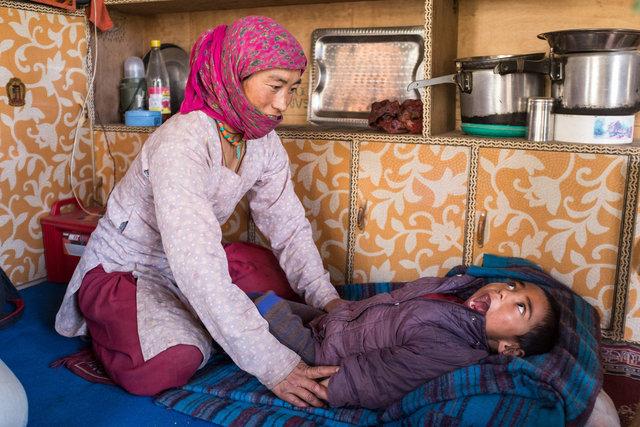 Eine Mutter macht Festhalteübungen mit ihrem an Zerebralparese erkrankten Sohn.