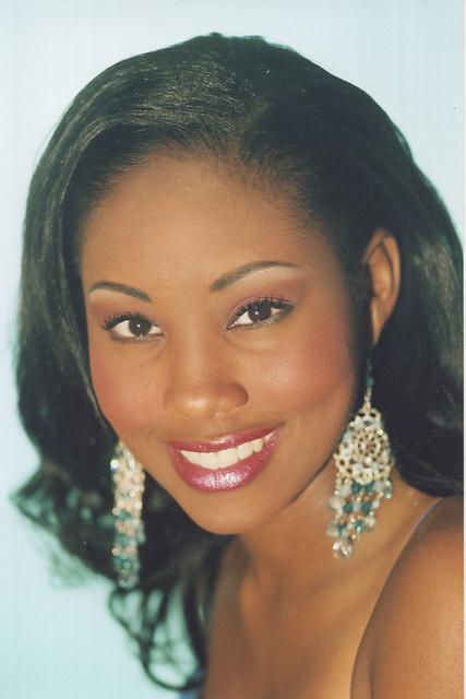 ARABIA wears silver and green drop earrings.