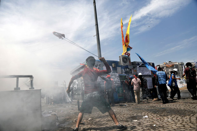 A protester throws a stone during clashes in Taksim Square