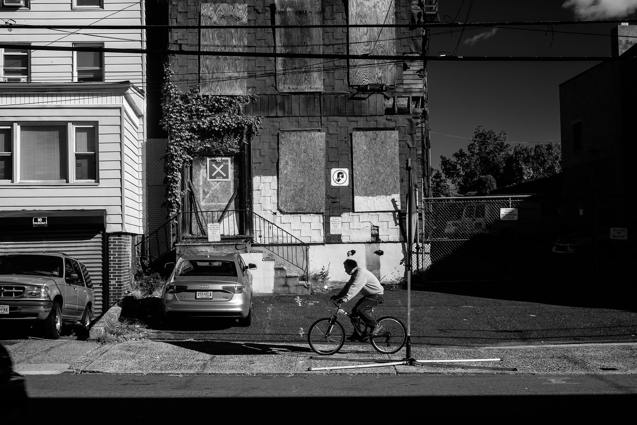 Man on bike rides past abandoned building.jpg