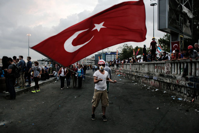 A protester waves a Turkish flag at Taksim square in Istanbul