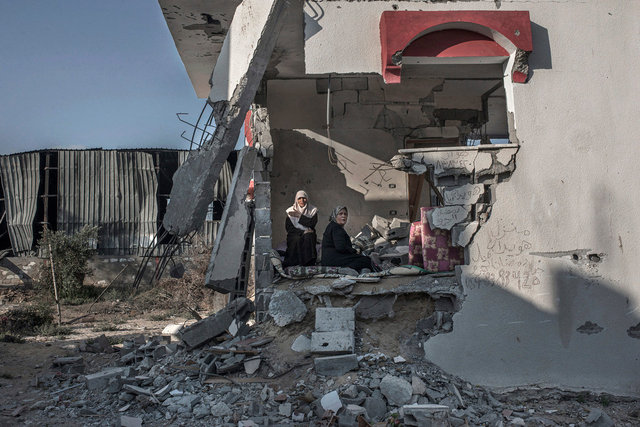 Two women in their destroyed house reading the Koran. Rafah. Gaza Strip