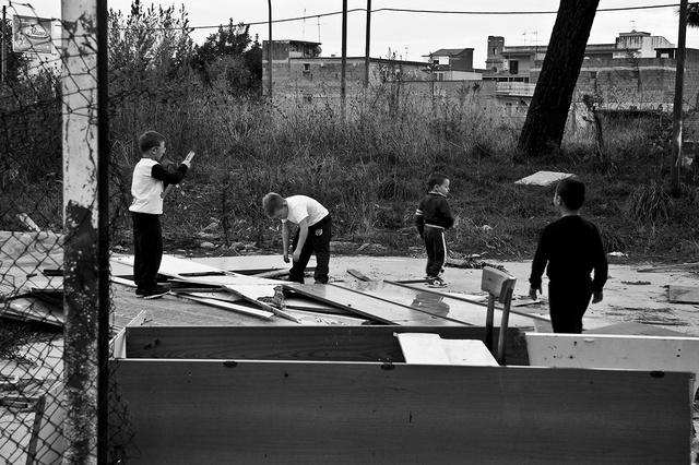 Bambini piccolissimi che giocano a costruire una capanna con scarti di mobili abbandonati nel parco