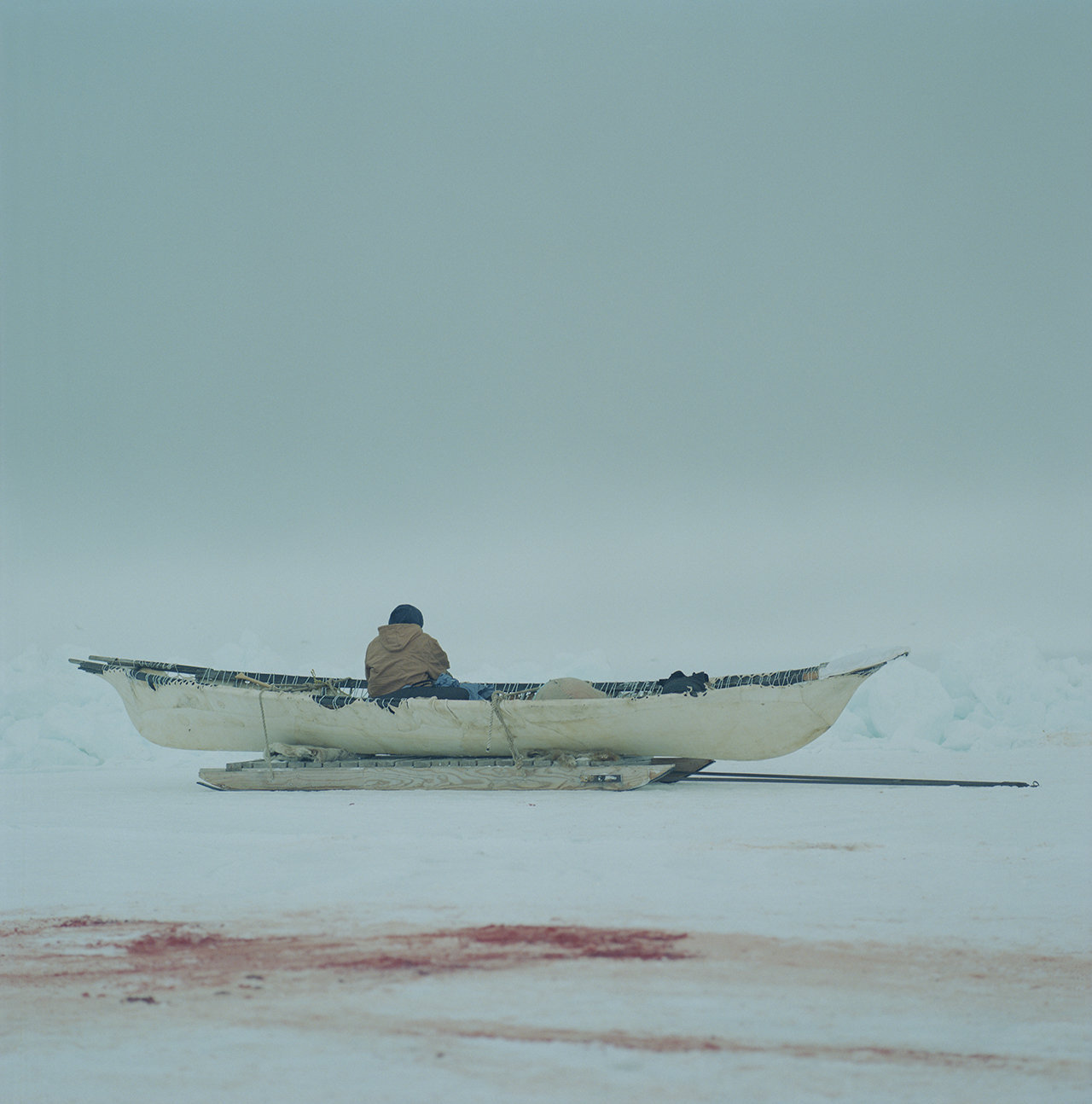 Man looking out over the lead in an umiak, 2012