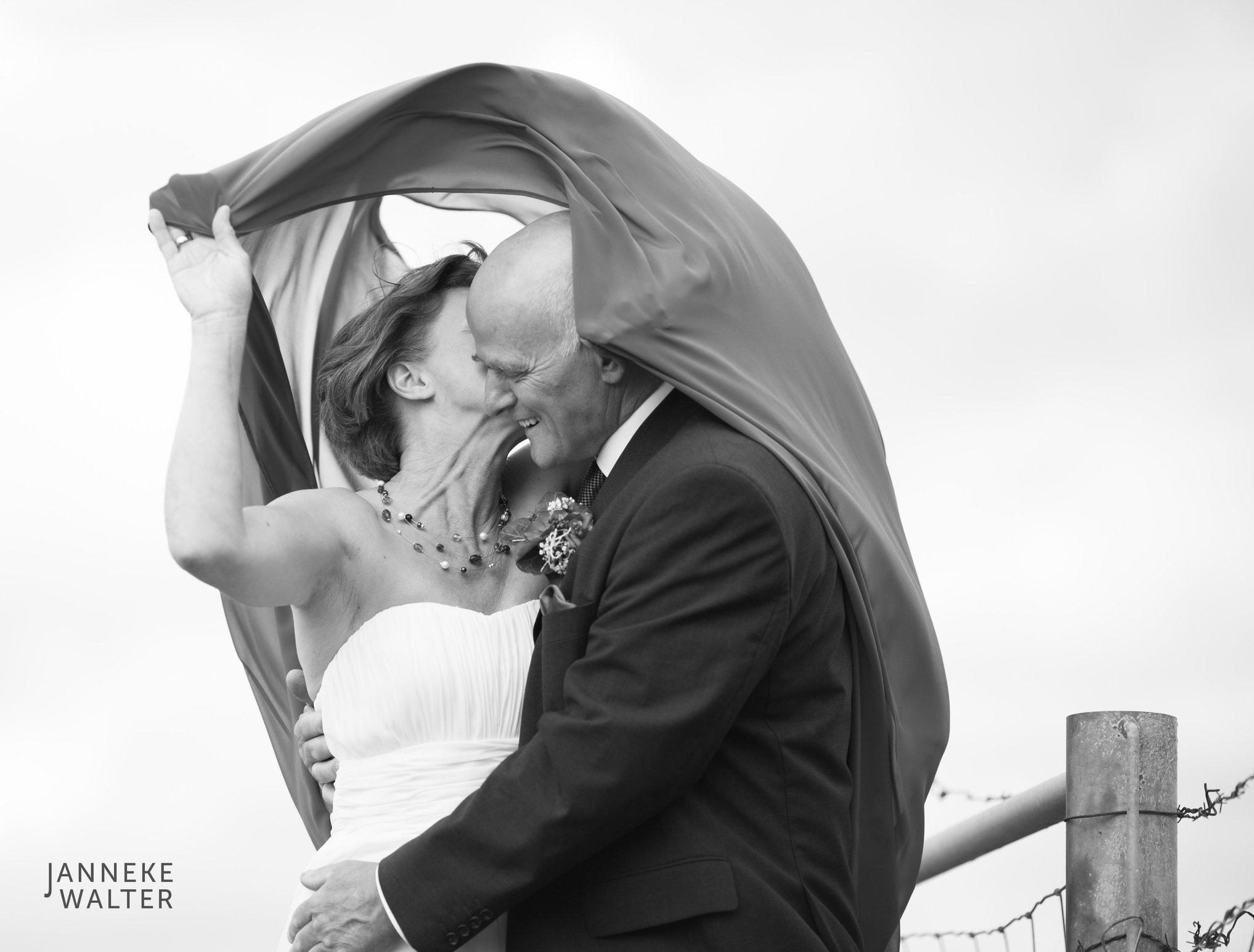 Portretfoto bruidspaar met stola in wind © Janneke Walter, fotograaf Utrecht De Bilt, loveshoot, bruidsfotografie, trouwfotografie