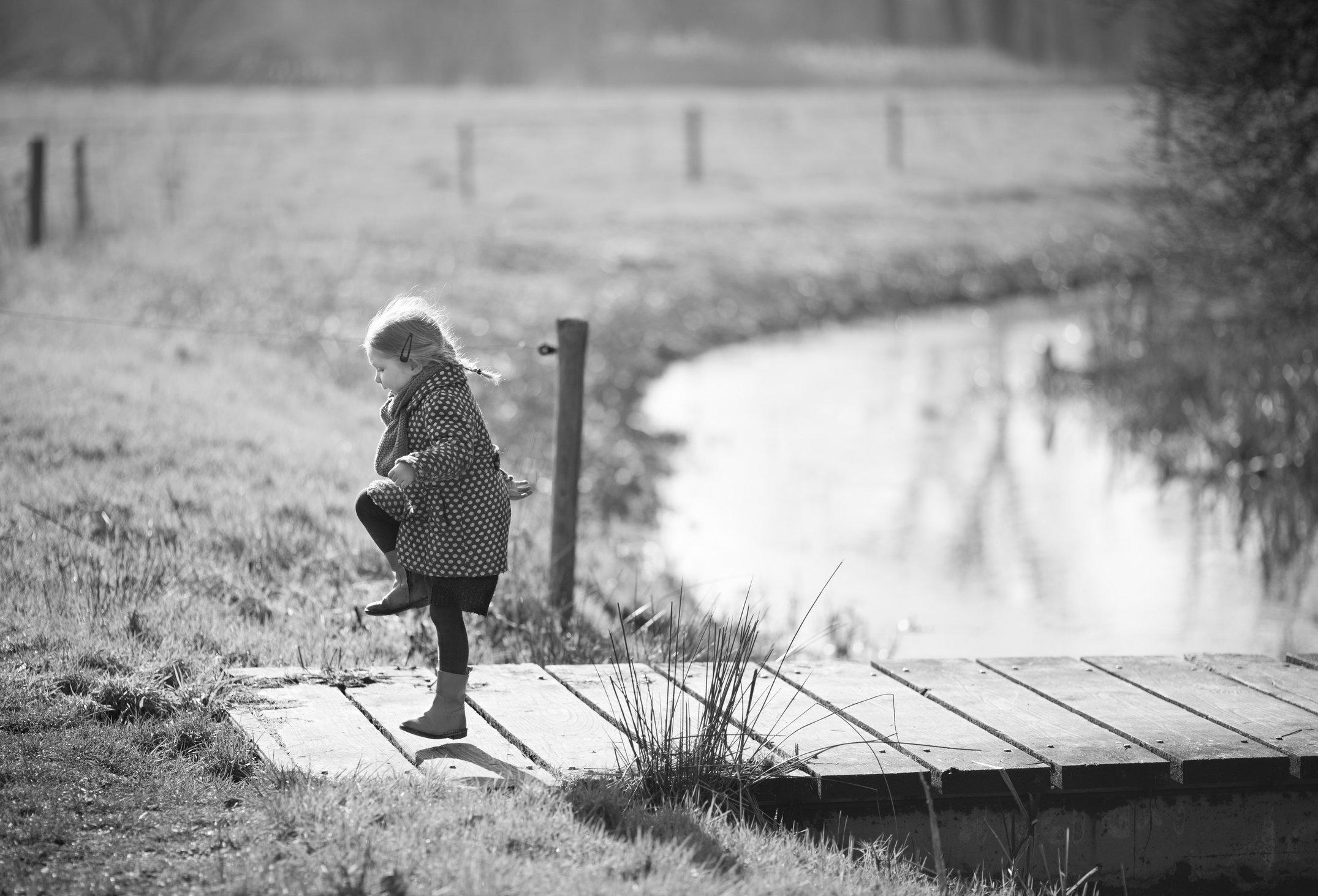 Portretfoto kind huppelend op brug