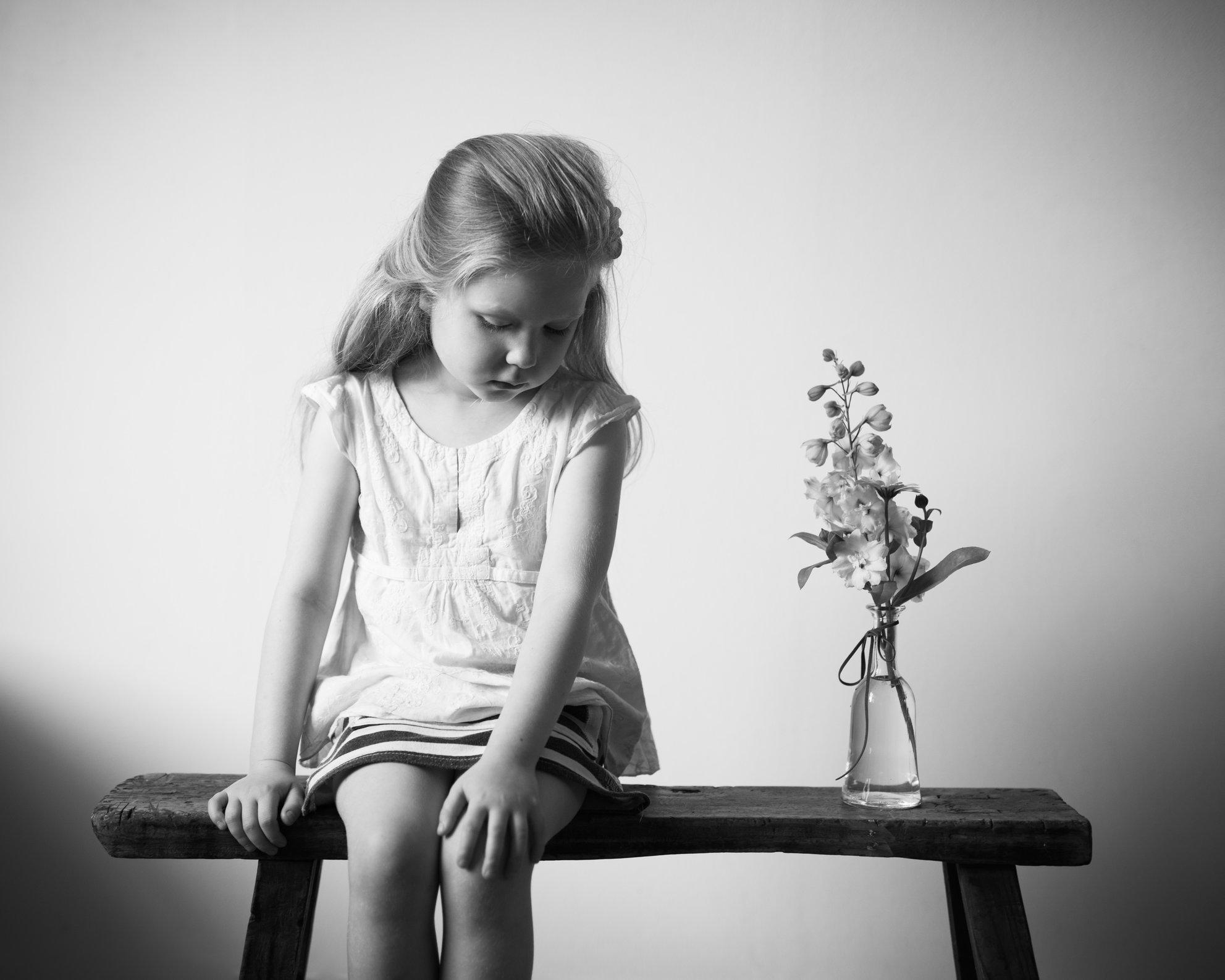 Portretfoto kind op bankje met vaasje bloemen - © Janneke Walter, kinderfotograaf omgeving Utrecht