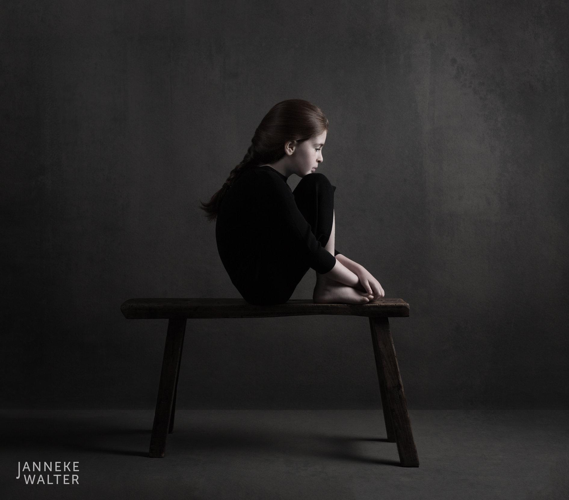 Portretfoto kind op bankje met opgetrokken knieën @ Janneke Walter, kinderfotograaf Utrecht De Bilt, kinderfotografie, kinderportret