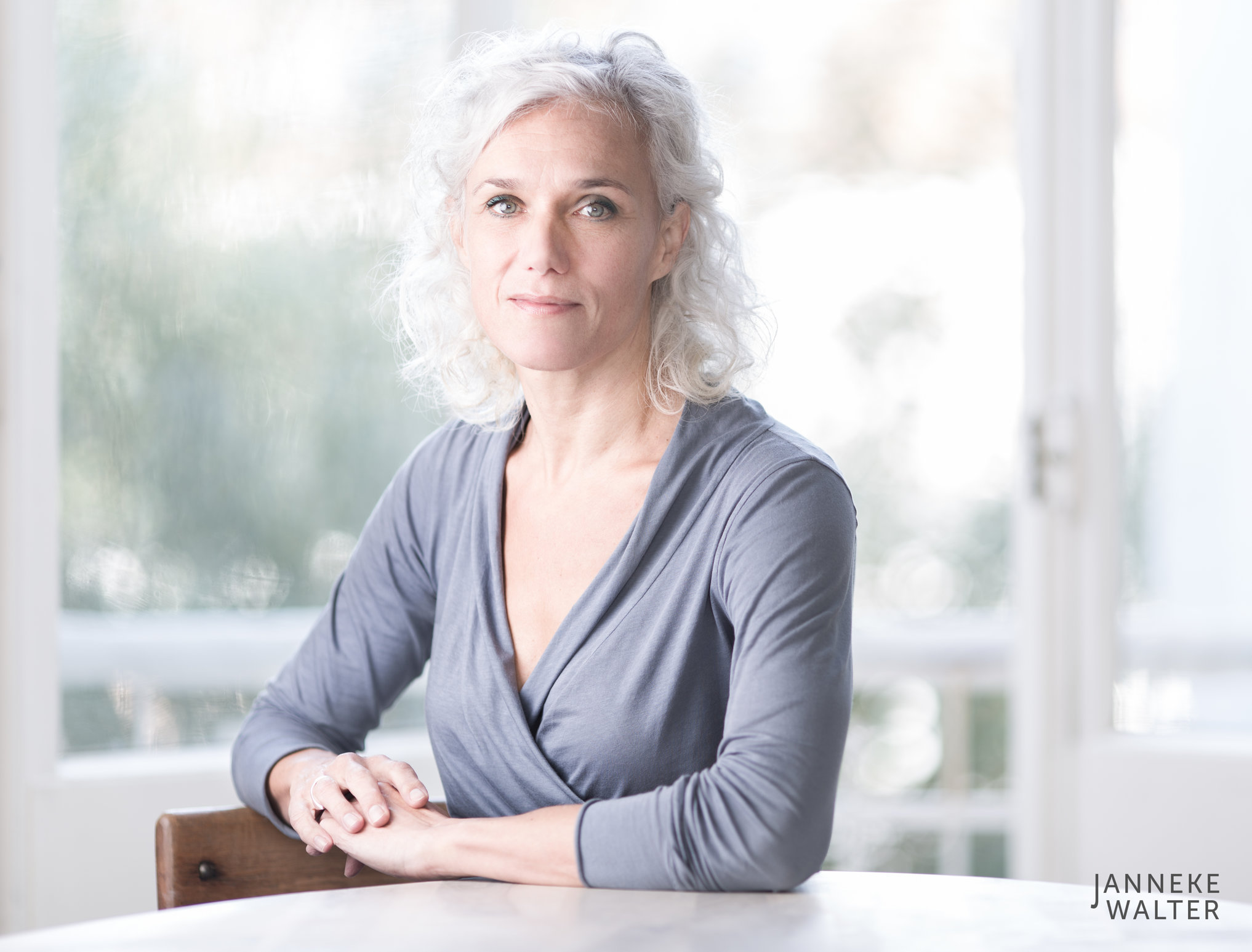 portretfoto vrouw aan tafel bij raam © Janneke Walter, fotograaf Utrecht De Bilt, portretfotograaf, portret, portretfotografie