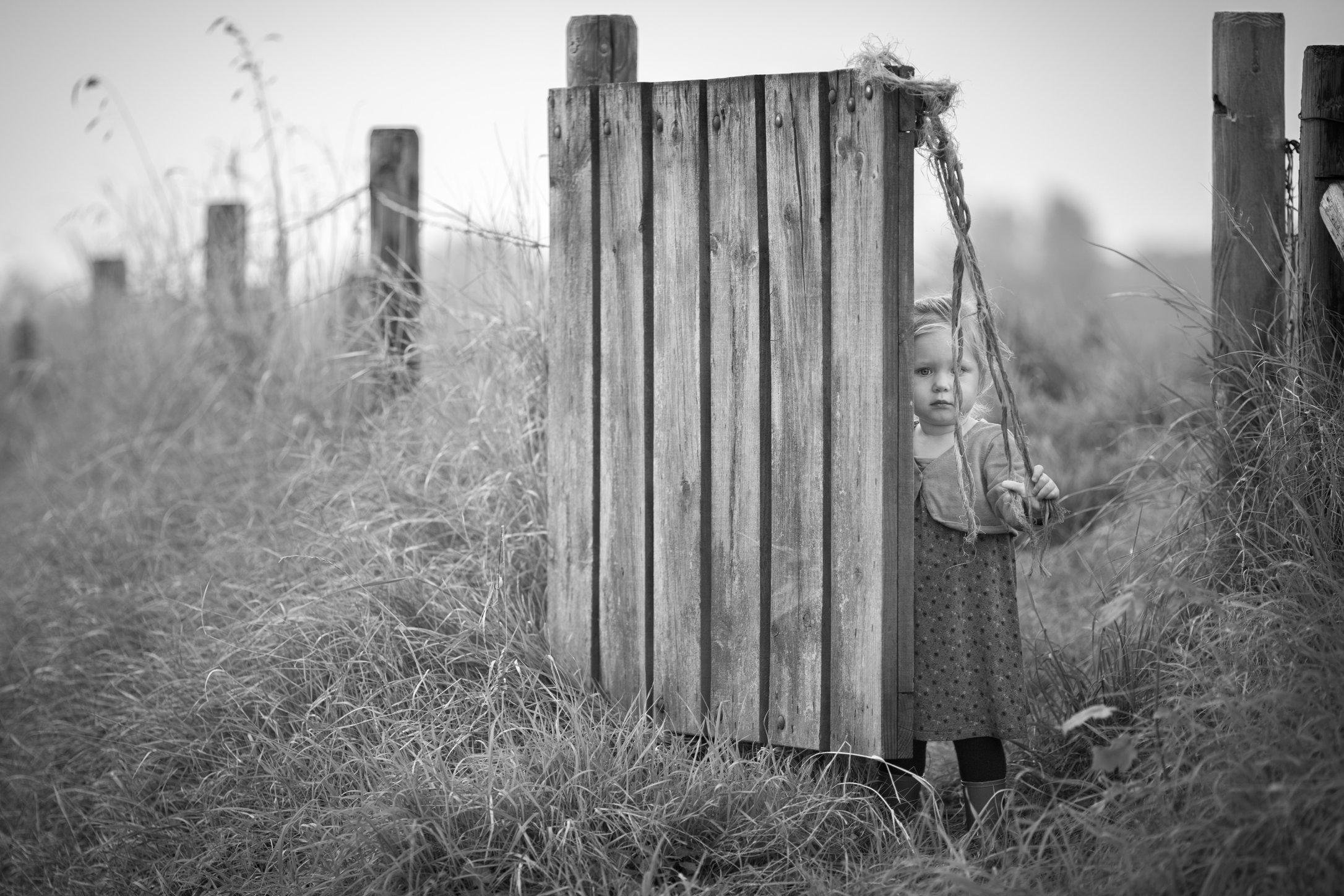 Portretfoto kind bij hek - © Janneke Walter, kinderfotograaf omgeving Utrecht
