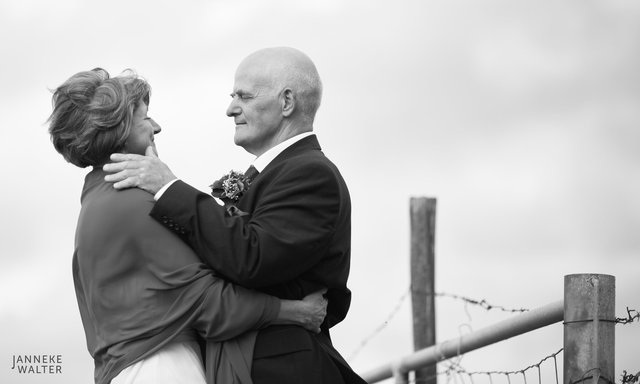 Portretfoto bruidspaar bij hek © Janneke Walter, fotograaf Utrecht De Bilt, loveshoot, bruidsfotografie, trouwfotografie