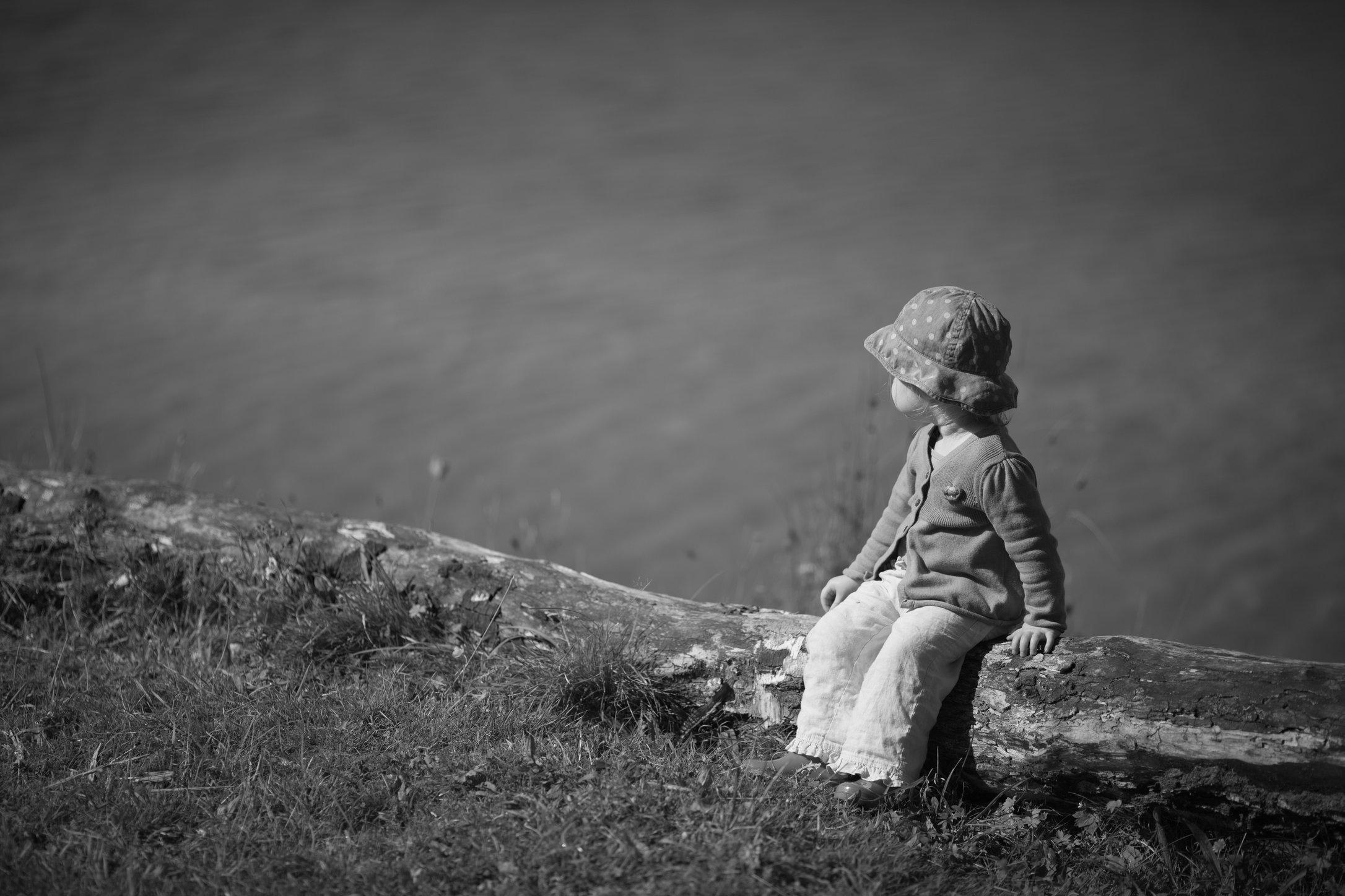 Portretfoto kind op boomstam bij meer - © Janneke Walter, kinderfotograaf omgeving Utrecht