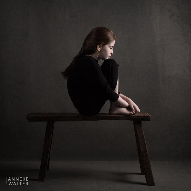 Fine art portretfoto kind op bankje met opgetrokken knieën @ Janneke Walter, kinderfotograaf Utrecht De Bilt, kinderfotografie, kinderportret, fine art fotografie