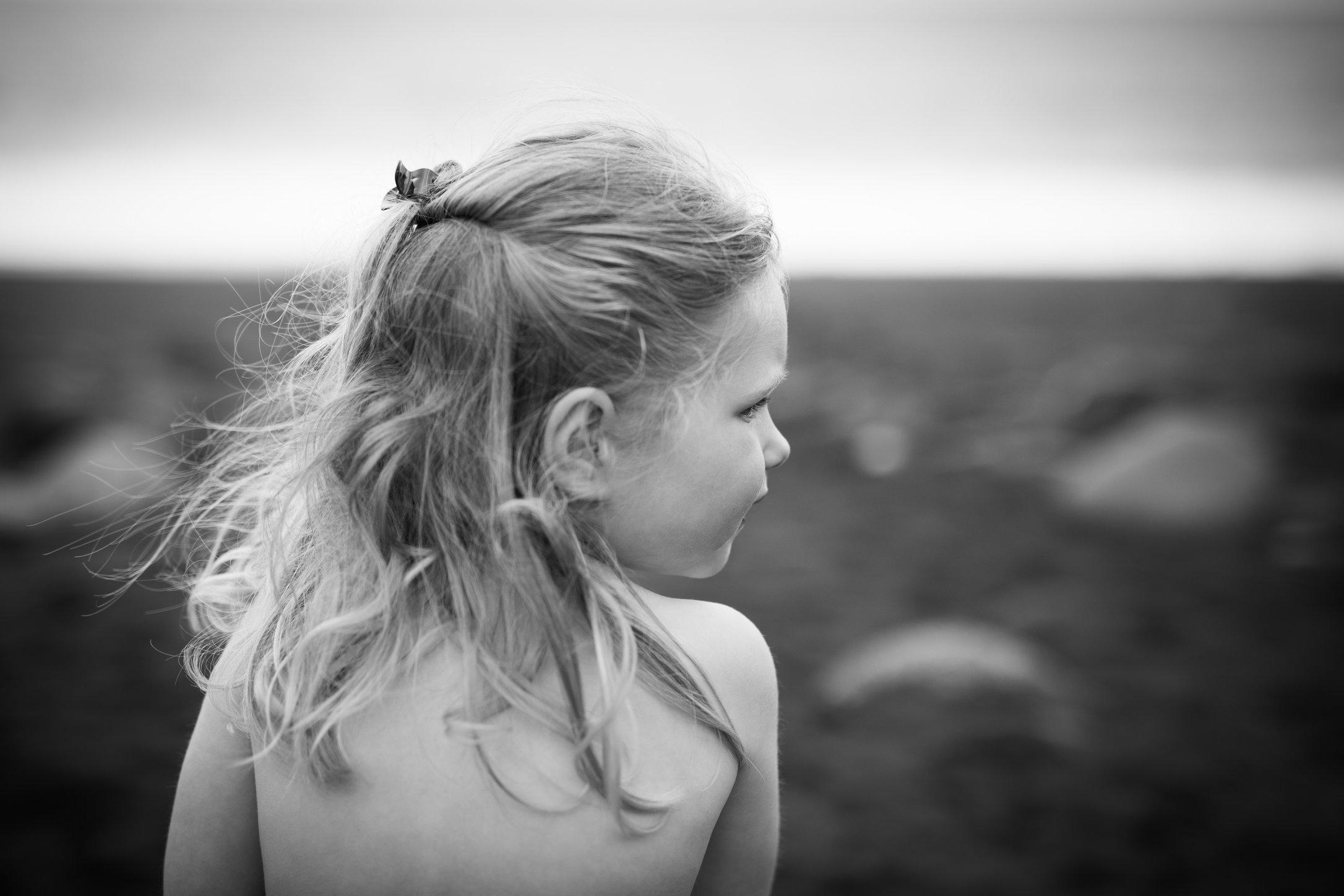 Portretfoto kind op lavastrand opzij kijkend