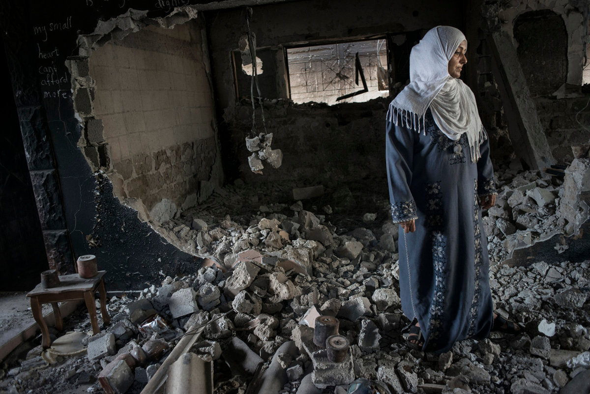 A woman in her destroyed house with some unexploded bombs.