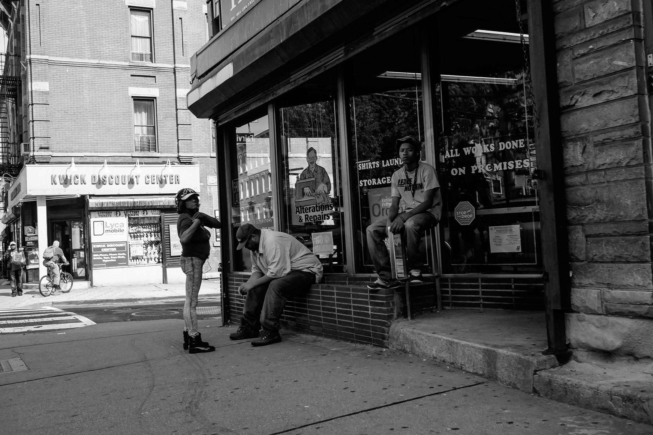 A group of people sit at the corner outside of an alteration shop.jpg