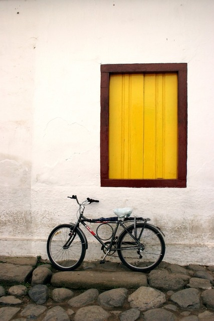 Fachada com janela amarela e bicicleta
