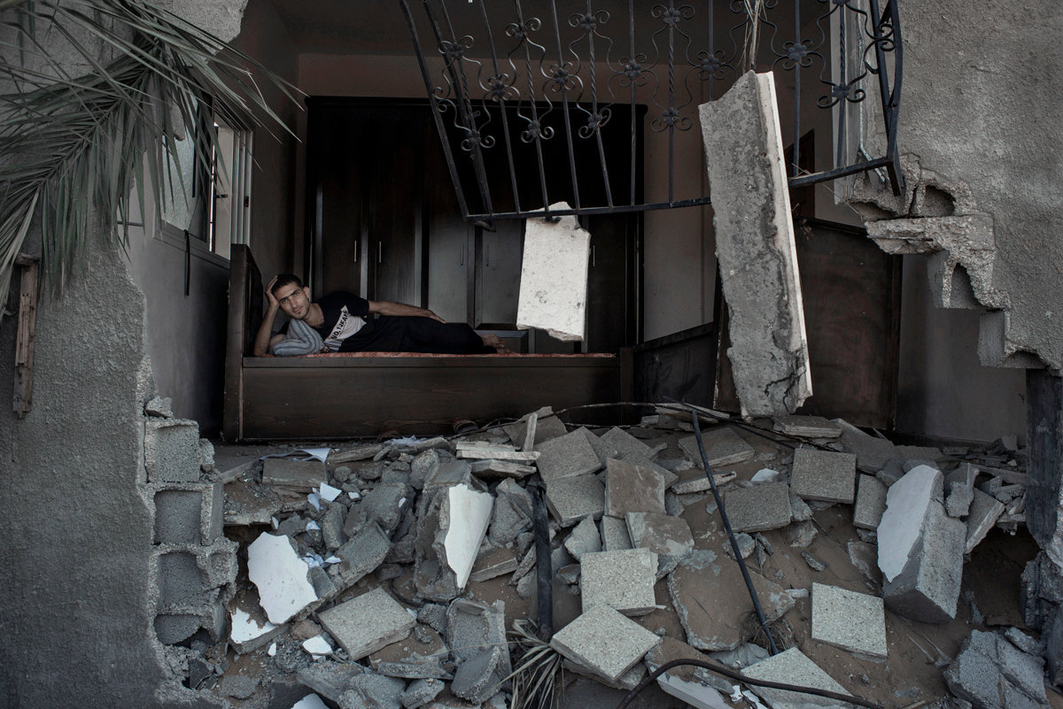 Walid Rouck , 24, amidst the rubbles of his neighbour's house in Khuzaa, Gaza Strip