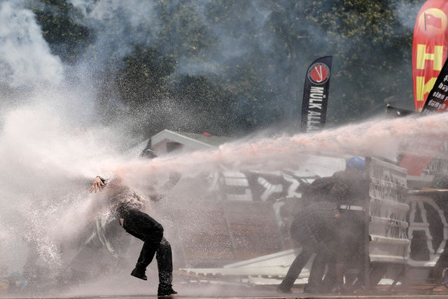 A man in a gasmask is hit by police water cannon.