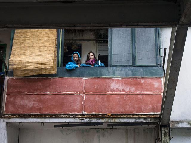 Due bambine affacciate al balcone nelle vele di Scampia